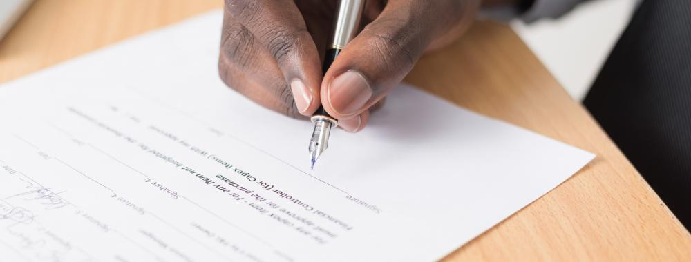 male hand filling out a form with a pen