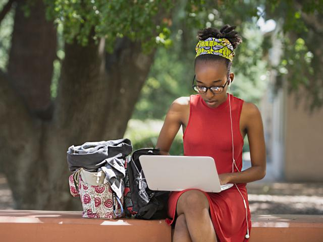 young female uc davis student outside working on a laptop